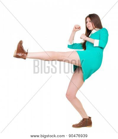 skinny woman funny fights waving his arms and legs. Isolated over white background. The girl in a dress beats foot in brown shoe.