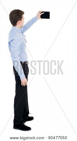 back view of standing business man with tablet computer in the hands of. Rear view people collection.   Isolated over white background. The guy in the office clothes photographed on a Tablet PC.