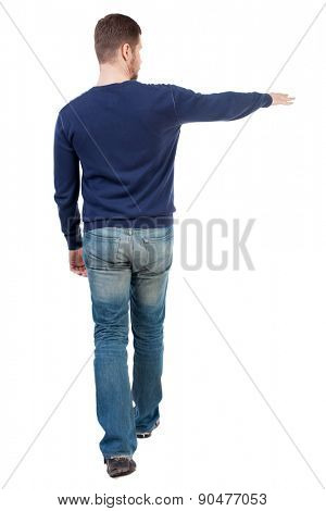 Back view of going  handsome man in jeans pointing. walking young guy . Rear view people collection.    Isolated over white background. The guy in jeans goes to the right showing the left