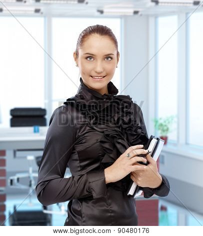 Portrait of elegant young female secretary at executive office, smiling.