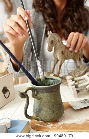 Closeup photo of painting female hand with paintbrush and wooden horse.