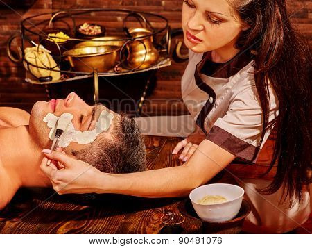 Man with clay facial mask in indian wooden beauty spa.