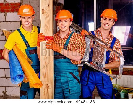 Happy group people men in builder uniform holding wooden boards .