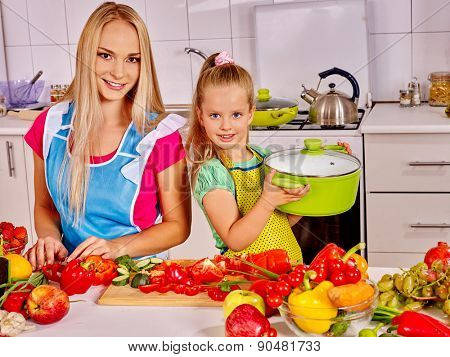 Mother and daughter cooking vegetables food at kitchen.