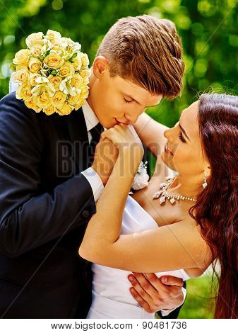 Bride and groom with flower summer  outdoor. Man kissing  girl hand