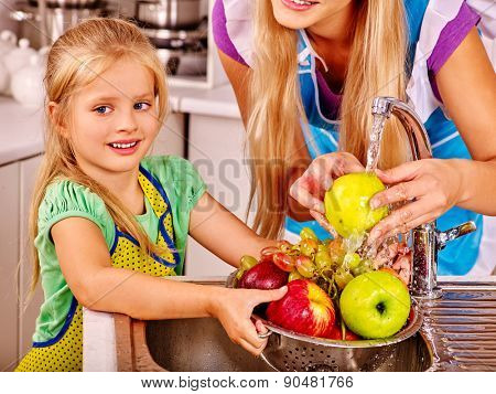 Mother and daughter washing fruit at kitchen. Kid help.