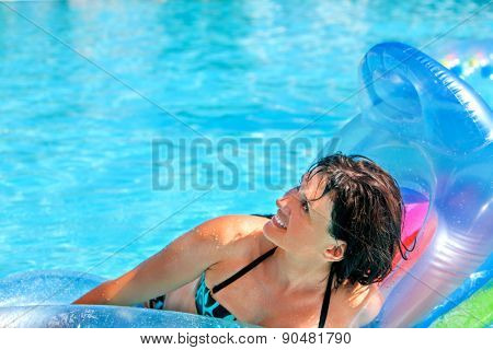 Happy woman  swimming on inflatable beach mattress. Looking up.