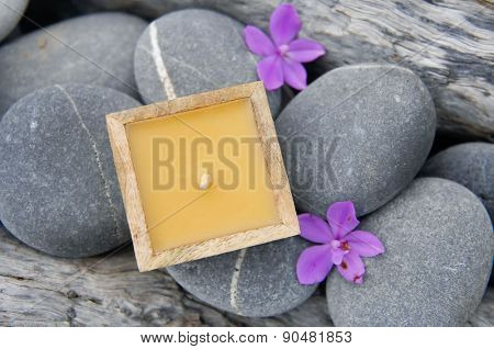 Purple orchid with candle ,old wood on pebbles