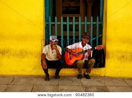TRINIDAD, CUBA - DECEMBER 24: Busker playing guitar and a man December 24, 2013 in Trinidad.