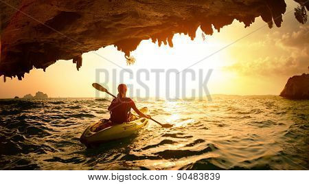 Young lady paddling the kayak in a sea near the cave exit