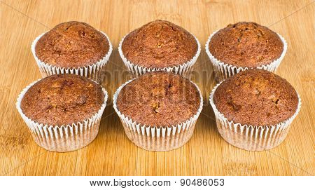 Six Muffins In Row On Wooden Board
