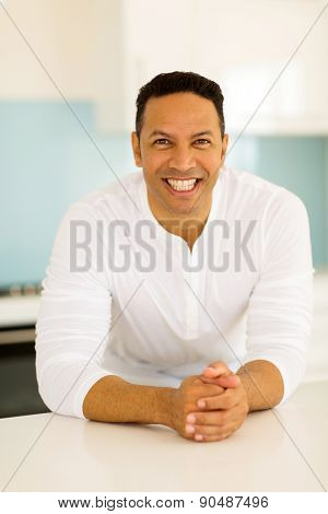 happy middle aged man leaning against the kitchen counter