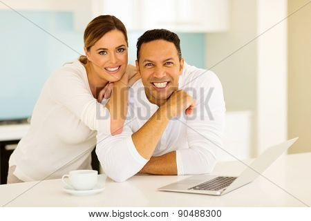portrait of happy couple leaning against the kitchen counter