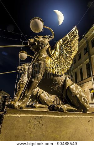 Griffins On Bank Bridge Across The Griboyedov Canal In Moonlight Night In St. Petersburg