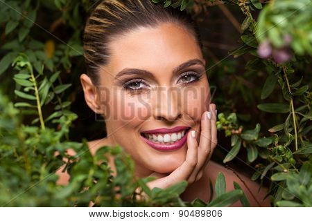 portrait of pretty blond woman behind leaves