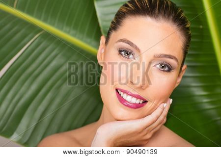 gorgeous woman with clean makeup over green leaf