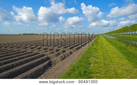 Canal along a plowed field with furrows in spring