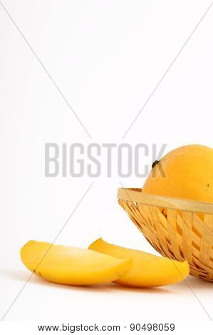 Mango fruit in basket with slice on white background