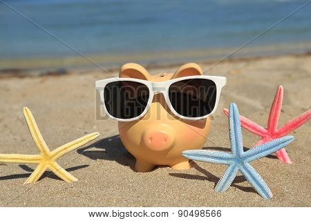 Summer piggy bank with sunglasses on the sand