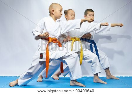 Three sportsmen are beating blows arms on a blue mats
