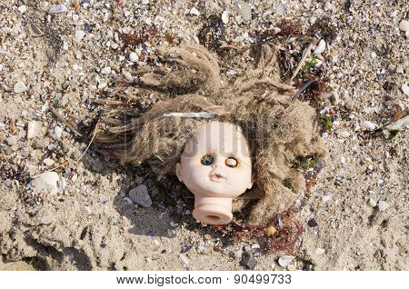 Head Of Children's Doll On The Beach Trash