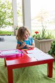 foto of kneeling  - Cute little girl kneeling down at a colorful vivid red table coloring in with pencil crayons on an outdoor undercover patio in spring or summer - JPG
