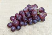 image of sackcloth  - bunch of ripe grapes on sackcloth background - JPG