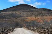 stock photo of canary-islands  - a road on wild volcanic landscape at Lanzarote Island Canary Islands Spain - JPG