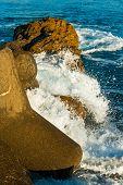 foto of breaker  - Waves been broken down over some rocks and man made wave breakers - JPG