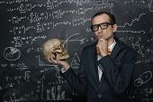 stock photo of math  - Funny smart nerd against chalkboard with many math formulas - JPG