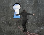 picture of keyholes  - Man balancing on old iron chain toward keyhole with sky clouds view and gray concrete wall background - JPG