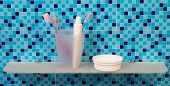 picture of toothpaste  - Tube of toothpaste and toothbrushes on glass shelf in bathroom - JPG