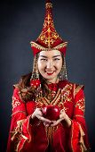 picture of national costume  - Woman in red national Kazakh costume holding red apple at grey background - JPG