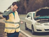 foto of towing  - Man calling car towing service on a highway roadside  - JPG