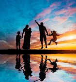 foto of time flies  - happy parents having good time with their little children on the seacoast - JPG