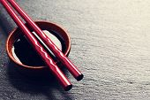 picture of soy sauce  - Japanese sushi chopsticks over soy sauce bowl on black stone background - JPG