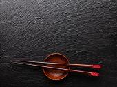 foto of soy sauce  - Japanese sushi chopsticks over soy sauce bowl on black stone background - JPG