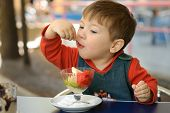 pic of hoodie  - Little boy in a red hoodie eats ice cream in the summer cafe - JPG