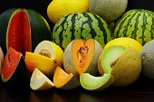 foto of honeydew melon  - Fresh melons on a dark wooden table - JPG