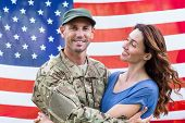 foto of reunited  - Handsome soldier reunited with partner against an american flag - JPG