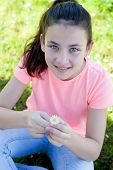 foto of preteen  - Happy casual preteen smelling a daisy at outside - JPG