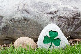 picture of shamrocks  - Decorative rock with an incised and painted green shamrock symbolic of Ireland the Irish Saint Patrick and the Holy Trinity standing on green grass with copyspace on the rock behind - JPG