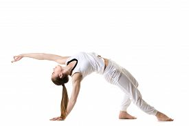 stock photo of pilates  - Young fitness model in white sportswear doing yoga or pilates training exercise bridge asana Camatkarasana Wild Thing Dancing Dog yoga pose side view - JPG