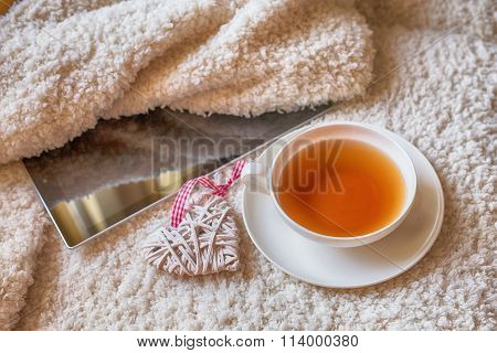 Cup Of Tea And Digital Tablet Over White Colored Textile Texture