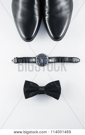 Black And White Minimalistic Composition: Men's Shoes, Watches, And The Bow Tie On A White Backgroun