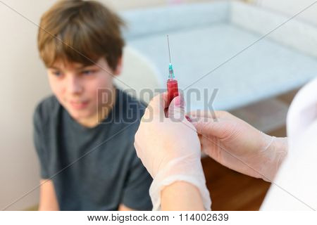 Woman hands holding a syringe with medicine for injection medicine, boy waiting for injection, focus on syringe