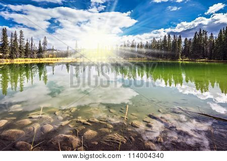 Jasper National Park in the Rocky Mountains of Canada. The morning sun brightly lights a landscape.   Multi-color autumn forest are reflected in the lake