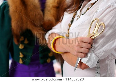 Female Fashion Designer Holding Big Golden Tailor Scissors In Hand Closeup