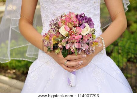 Bridal Bouquet Of Purple Flowers In The Bride's Hands