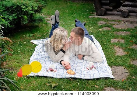 Portrait Of A Young Heterosexual Couple Walking On The Park, Embraced, Looking At Each Other